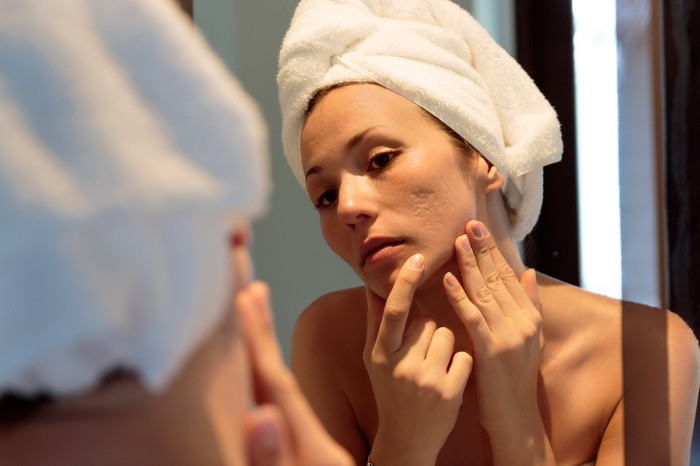 Woman with her hair wrapped in a towel examines her face in mirror.