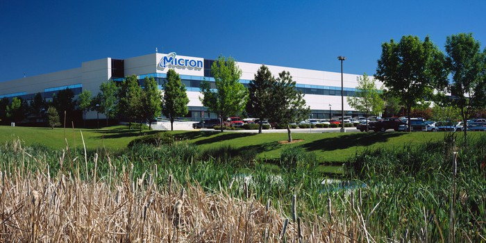A Micron building surrounded by low grassy hills and trees.