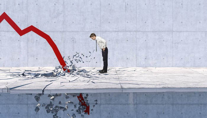A businessman leans forward to get a closer look at a large red charting arrow crashing down through the floor at his feet.