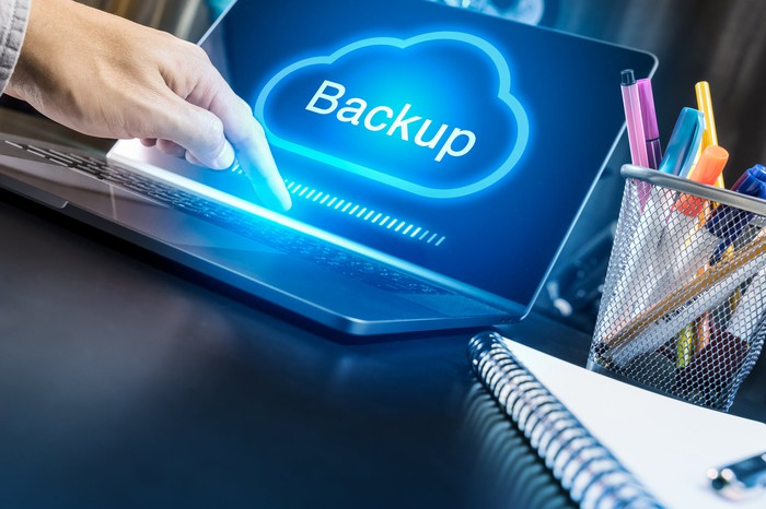 Person backing up data on a laptop to the cloud