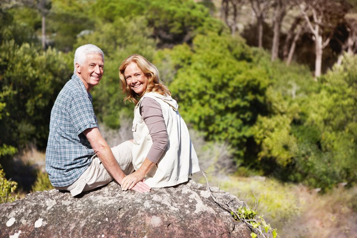 Smiling older man and woman sitting on a rock surrounded by trees.