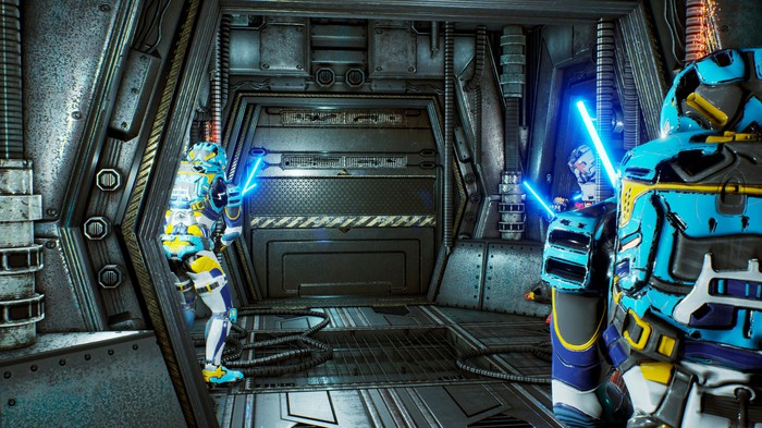 Four soldiers in space suits holding light sabers wait outside a space ship door