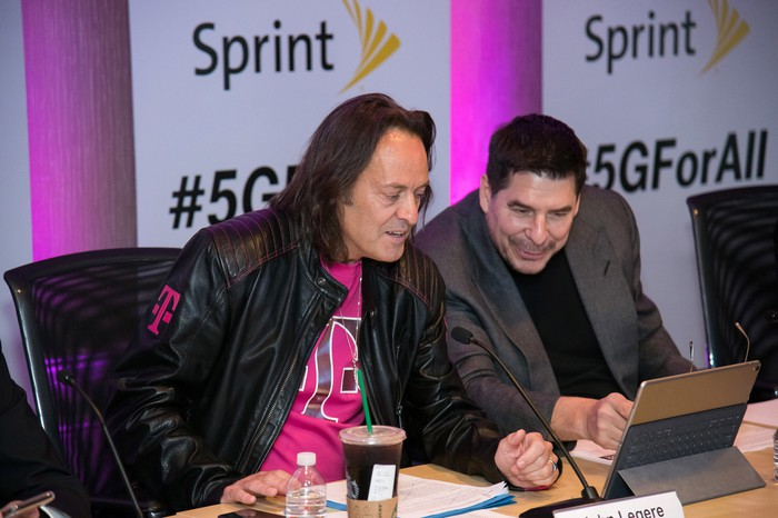 John Legere and Marcelo Claure sitting next to each other behind a table