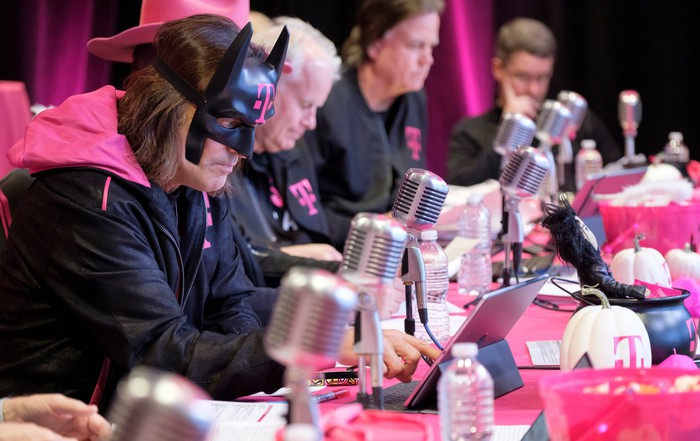 John Legere wearing a Batman mask with the T-Mobile logo during an earnings call