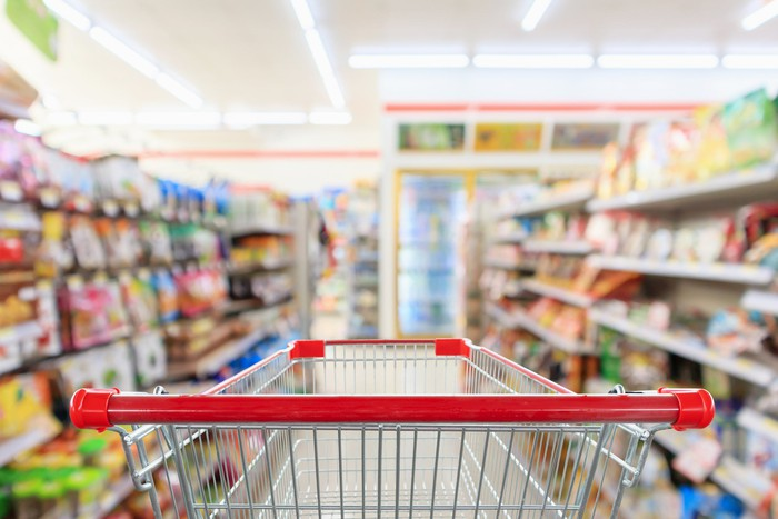 Shopper's-eye view of a grocery shopping cart at the head of a store aisle.