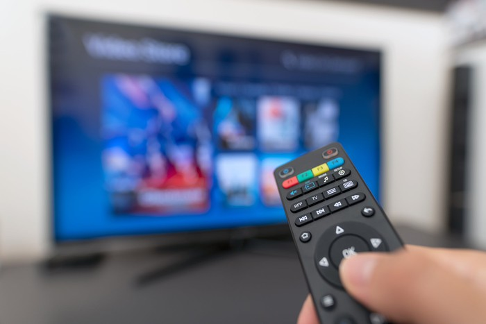 Hand holding remote in front of a TV with blurred streaming options