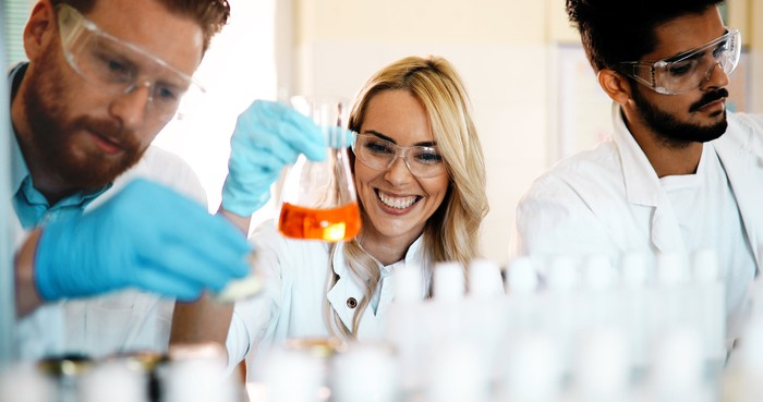 Three scientists in lab working with test tubes