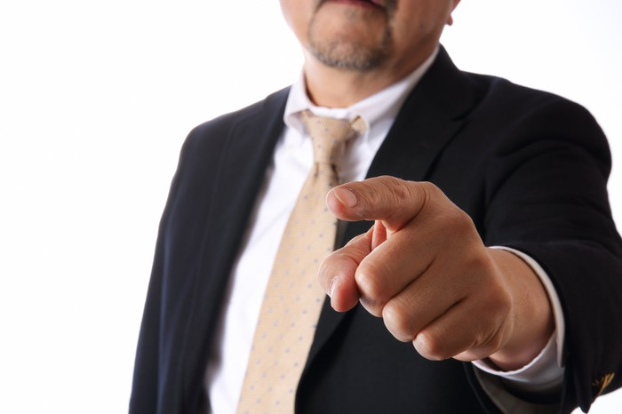 A business man with his finger pointed out