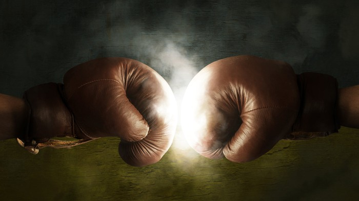 Two boxing gloves colliding.