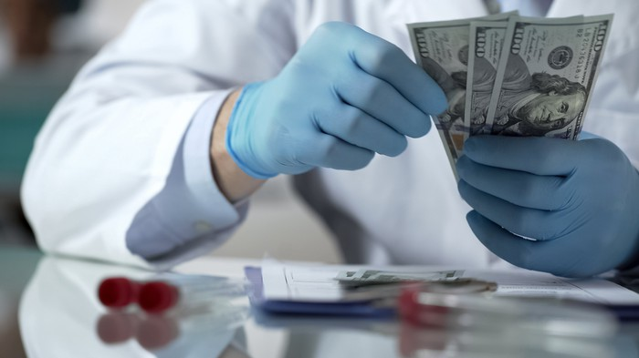 Person in a lab coat sitting on a workbench while counting hundred-dollar bills with his gloved hands.