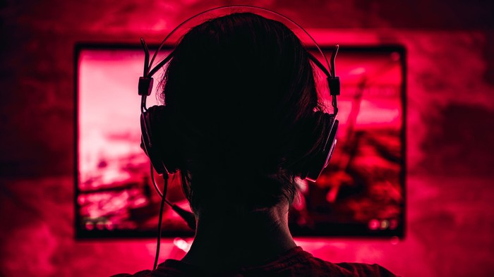 A person playing video games in a dark, red lit room