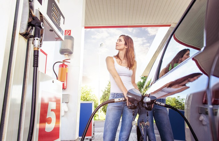 A young woman filling up her car at a gas station.