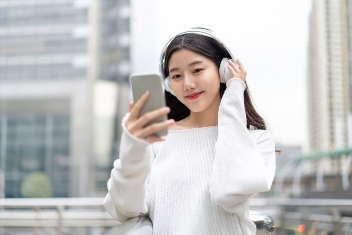 A young woman listens to music on her smartphone.