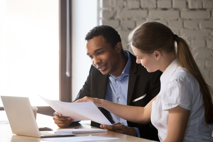 Female salesperson consulting with a male client about loan paperwork.