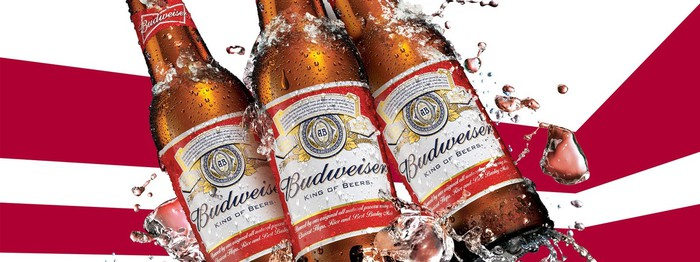 Three bottles of Budweiser against a red and white background.