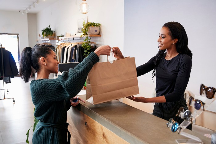 Woman on one side of a retail counter handing a shopping bag to a woman on the other side of the counter