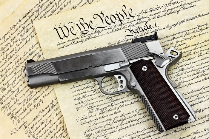 A handgun lying on top of the U.S. Constitution