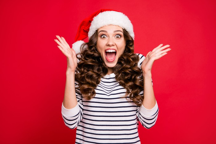 Woman wearing a Santa hat, holding up her arms and sporting an excited expression