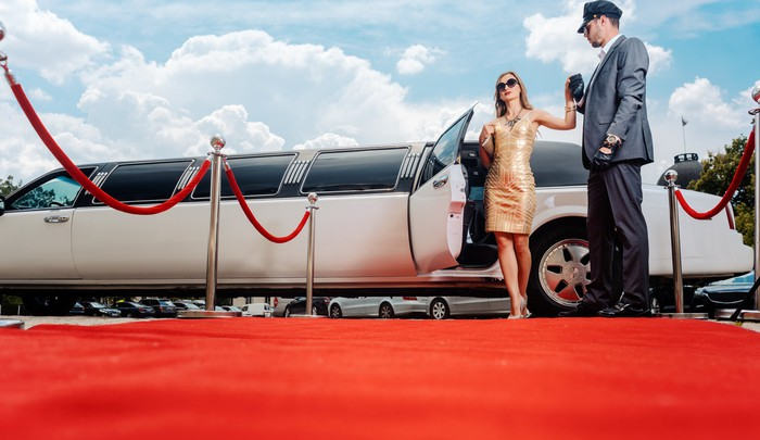 A well-dressed woman, with her hand being held by a chauffeur, stepping out of a limousine and onto a red carpet.