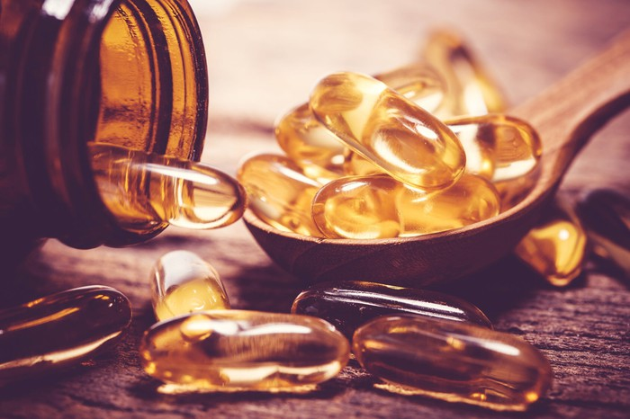 About a dozen fish oil tablets in a wood spoon, with bottle nearby.