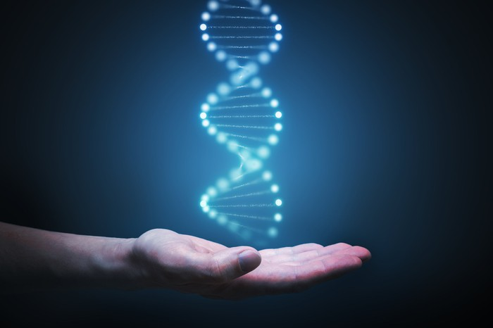 An image of a DNA helix over the outstretched palm of a person's hand