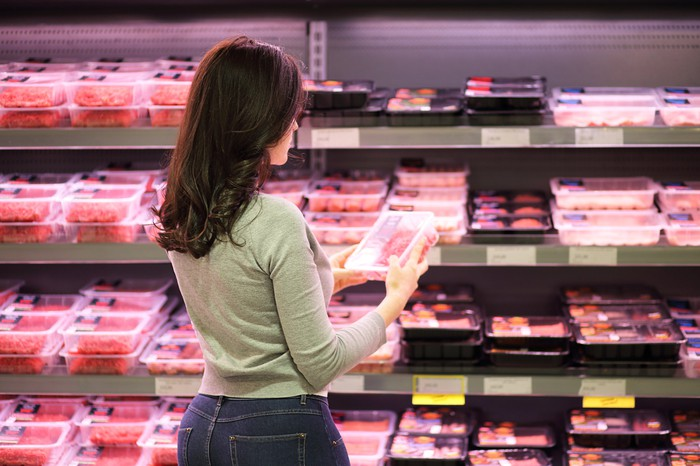 Woman shopping for meat products in a grocery store.