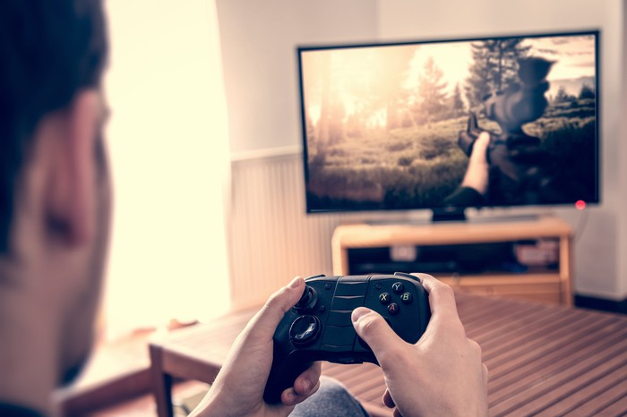 Person playing a first-person shooter video game on a television