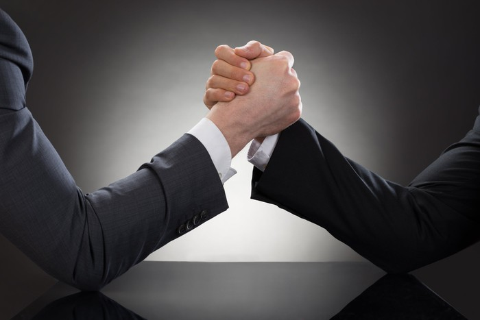 Close-up shot of two arms in business jackets arm-wrestling on a black table.