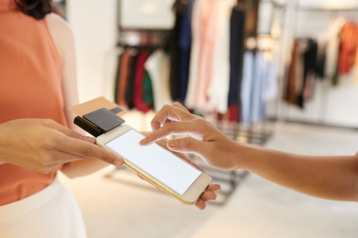 A shopper pays for clothing via a tablet