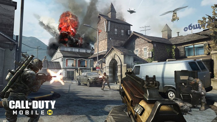 A first-person view of a character holding a gun and looking at a battleground in Call of Duty: Mobile.