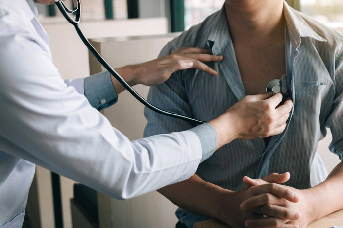 Doctor pressing stethoscope against man's chest
