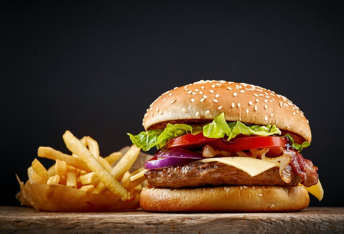 A juicy hamburger with fries on a chopping board.