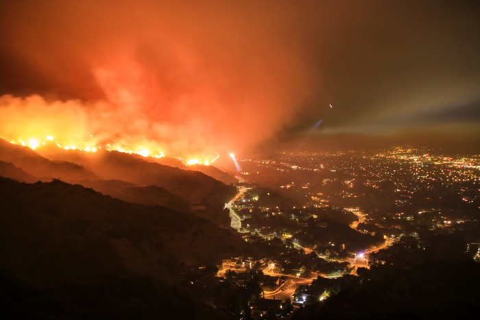 A wildfire around a city at night time