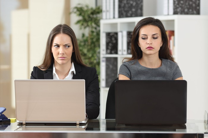 Two women seated next to each other at laptops giving each other dirty looks