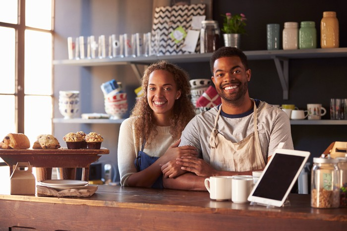 Young smiling couple standing behind coffee shop counter