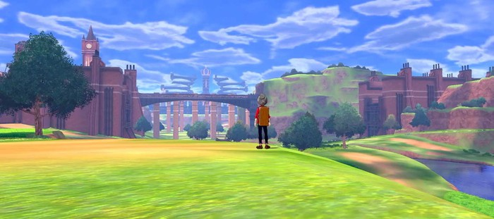 A player-character in the latest Pokemon game standing on a hill and looking at a bridge and castle in the distance.