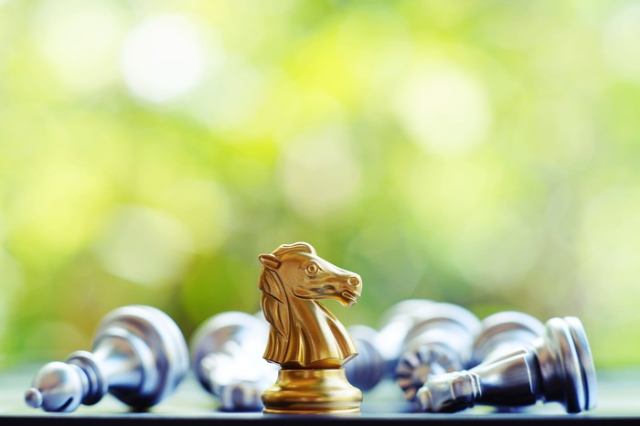 One gold knight stands alone on a chess board, surrounded by several silver pieces lying down.