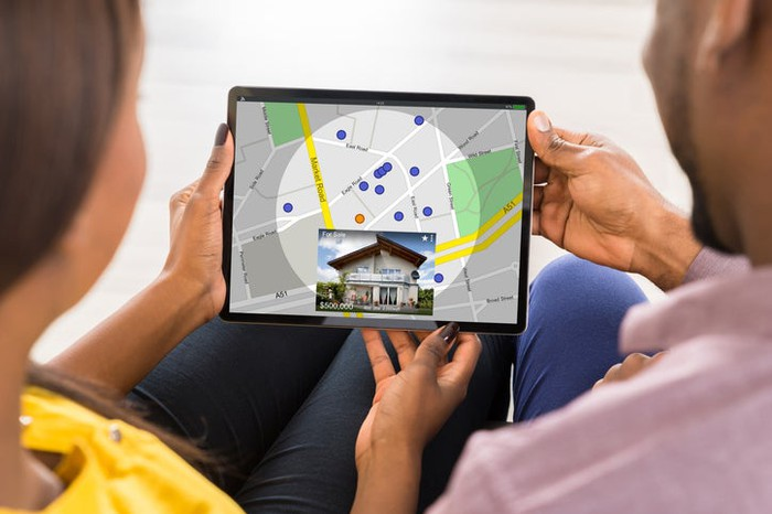 Two people browse for a home online using a tablet.