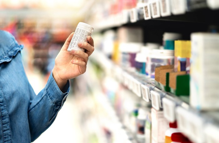 Customer standing in a pharmacy aisle holding a pill bottle