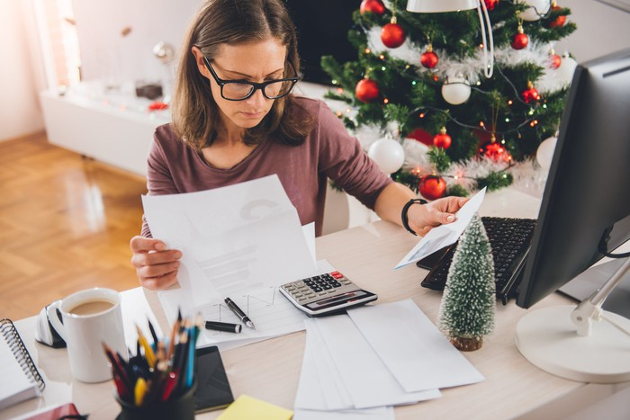 Woman seated at desk looking at papers with a concerned expression while a Christmas tree stands in the background