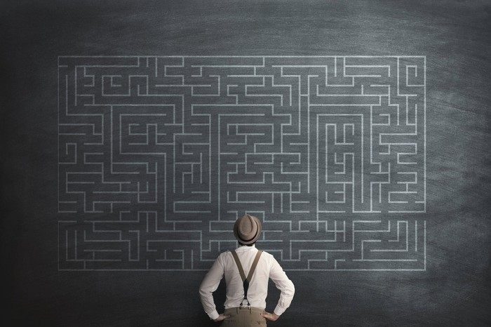 A man looks at an illustration of a massive maze.