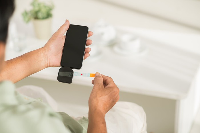 A patient measuring their blood glucose level with a add-on attached to their phone.