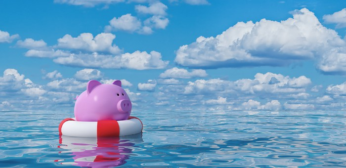 A pink piggy bank in a life buoy floating in the open ocean.