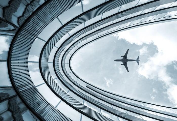 An aircraft flies over a modern office building on approach for landing.