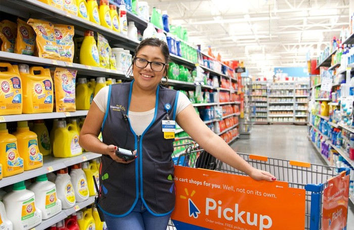 Walmart associate smiling with her hand on a shopping cart while filling a pickup order.