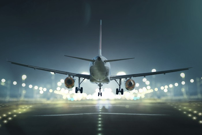 An airplane lands on a brighly lit runway at night.