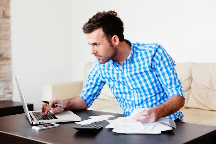Man at laptop with papers and calculator spread out in front of him