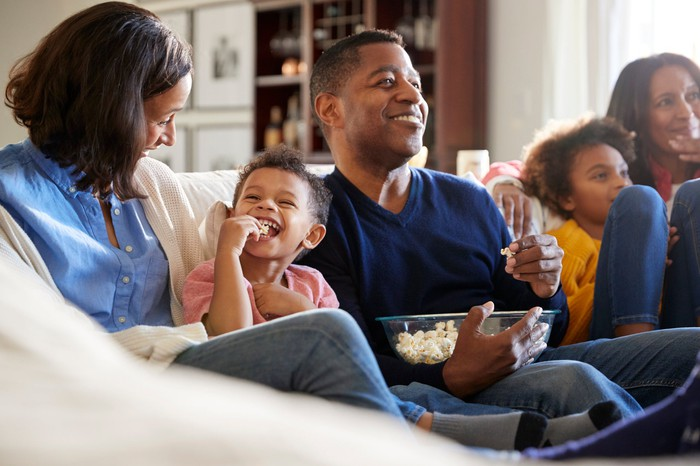 A smiling family watching TV on a couch and eating popcorn