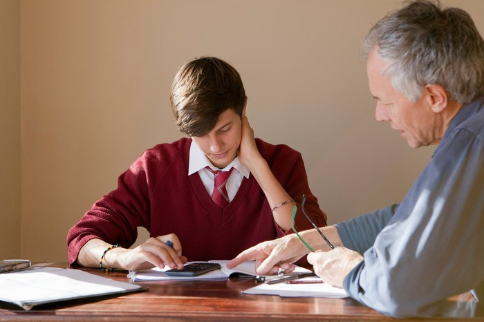 Teenager looks down at calculator and notebook while older man points and looks on