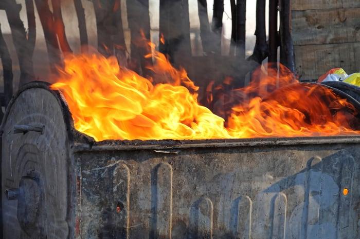 Fire blazing in a garbage dumpster.